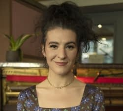 Color bio photo of Jesse Paris Smith standing in front of a piano wearing dark flowered dress and necklace smiling into camera.