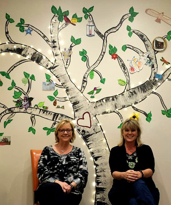 Amber and Julee sitting in front of the memory tree on the wall of their space.