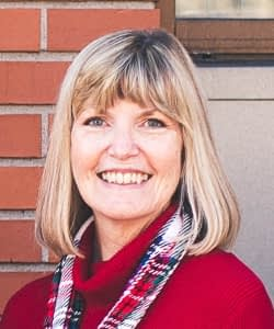 Maribeth Doerr in red shirt and multicolor scarf smiling at camera standing in front of brick wall outside.